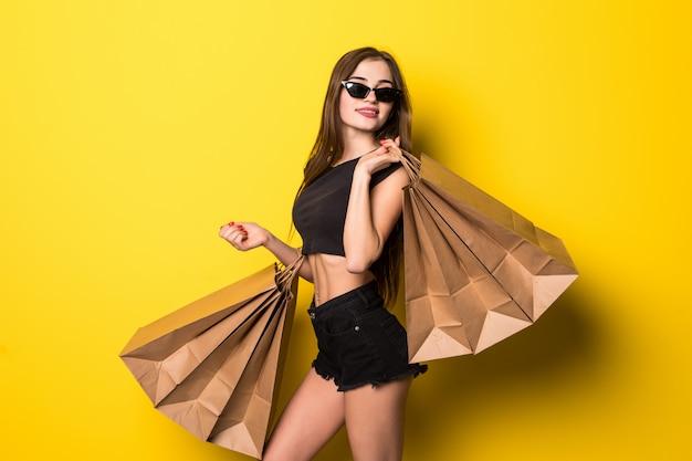 Młoda kobieta stojąca na białym tle nad żółtą ścianą trzymając torby na zakupy