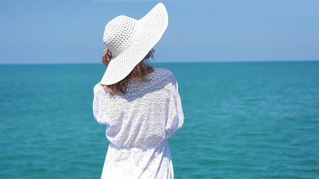 Młoda kobieta stojąca na piasku w pobliżu morza i trzymająca biały kapelusz