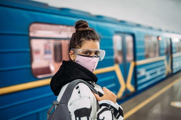 Młoda kobieta stojąca na stacji w medycznej masce ochronnej