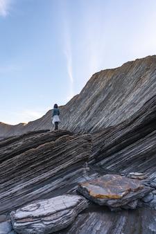 Młoda kobieta stojąca na szczycie kamieni w geoparku wybrzeża sakoneta