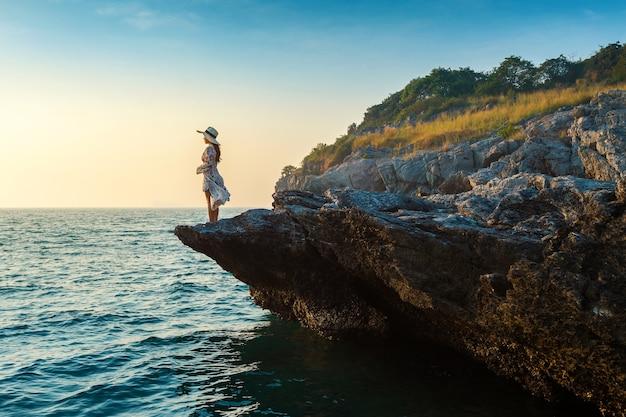 Młoda kobieta stojąca na szczycie skały i patrząc na brzeg morza i zachód słońca na wyspie si chang.
