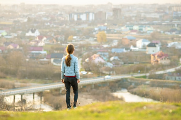 Młoda kobieta stojąca na zewnątrz, ciesząc się widokiem na miasto. koncepcja relaksu, wolności i dobrego samopoczucia.