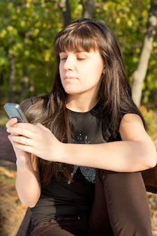 Młoda kobieta stojąca na zewnątrz w słonecznym lesie, czytając wiadomość tekstową na ekranie swojego telefonu komórkowego