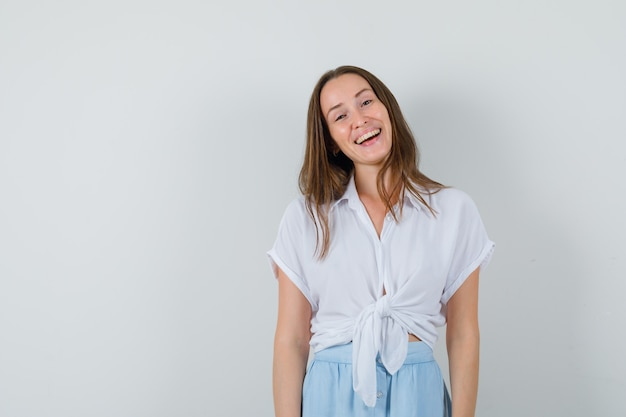 Młoda kobieta stojąca prosto i śmiejąca się w białej bluzce i jasnoniebieskiej spódnicy i wyglądająca wesoło