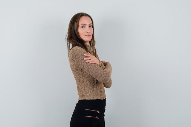 Młoda kobieta stojąca prosto i trzymając ręce skrzyżowane na piersi w pozłacanym swetrze i czarnych spodniach, wygląda atrakcyjnie