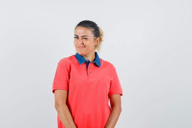 Młoda kobieta stojąca prosto, mrugająca i pozująca w czerwonej koszulce i ładnie wyglądająca. przedni widok.