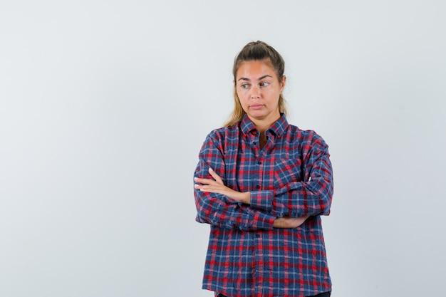 Młoda kobieta stojąca prosto, odwracająca wzrok i pozująca z przodu w koszuli w kratkę i zamyślona