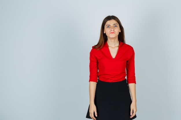 Młoda kobieta, stojąca prosto, pozując w czerwonej bluzce