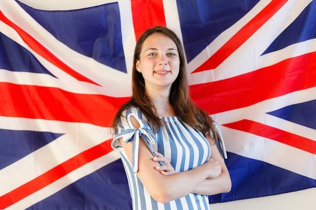 Młoda kobieta stojąca przed flagą wielkiej brytanii
