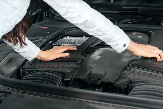 Młoda kobieta stojąca przed samochodem z otwartą maską patrząca pod maskę samochodu car