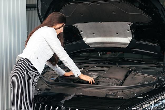 Młoda kobieta stojąca przed samochodem z otwartą maską w garażu zaglądająca pod maskę samochodu car