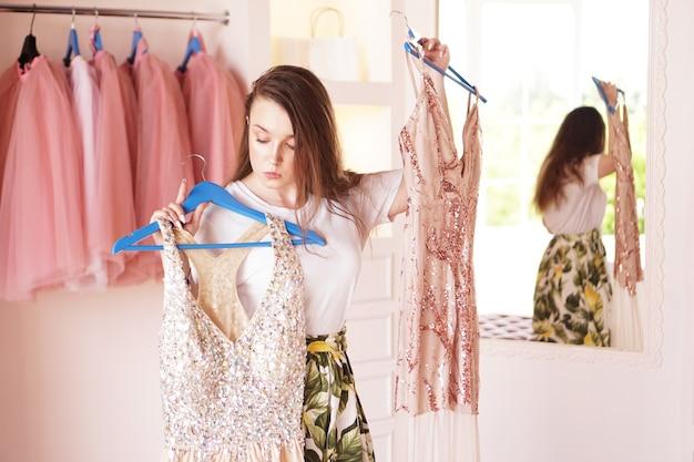 Młoda kobieta stojąca przy szafie, trzymająca sukienkę na wieszakach, próbująca zdecydować, w co się ubrać. ładna kobieta wybierając ubrania w garderobie.