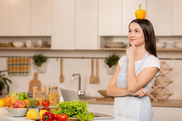 Młoda kobieta stojąca w kuchni z laptopem, mając pomysł i patrząc przepisy kulinarne w kuchni. bawić się. widok z boku