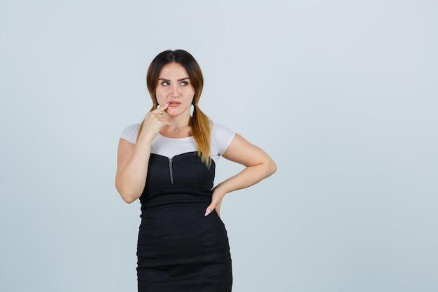 Młoda kobieta stojąca w myślącej pozie i kładąca palec wskazujący w pobliżu ust