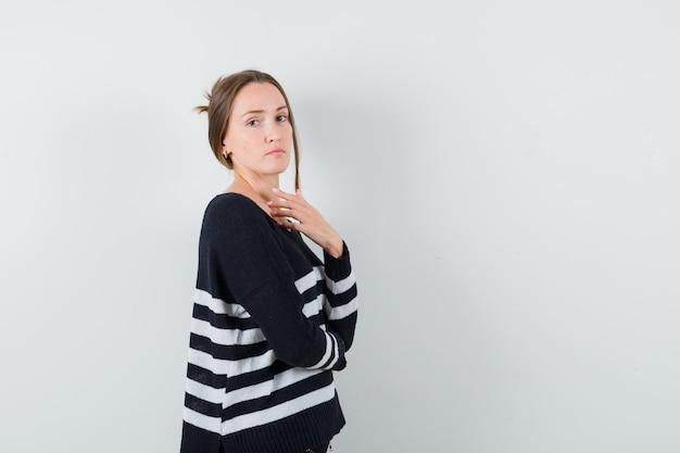 Młoda kobieta stojąca w myślącej pozie i patrząc przez ramię w pasiastej dzianinie i czarnych spodniach i wyglądająca pewnie