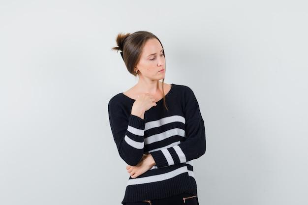 Młoda kobieta stojąca w myślącej pozie i patrząc w prawo w pasiastej dzianinie i czarnych spodniach i patrząc skupiona