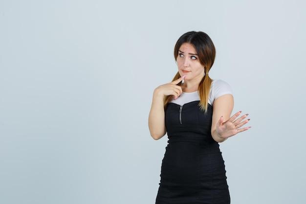 Młoda kobieta stojąca w myślącej pozie, pokazując palmę