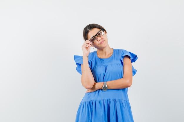 Młoda kobieta stojąca w myślącej pozie w niebieskiej sukience i wyglądająca na inteligentną