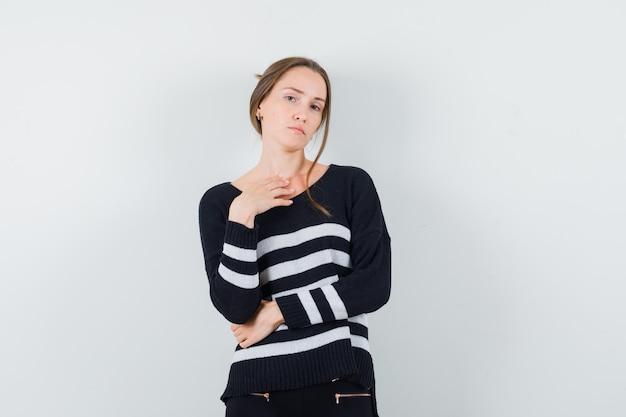 Młoda kobieta stojąca w myślącej pozie w pasiastej dzianinie i czarnych spodniach i patrząc zamyślony