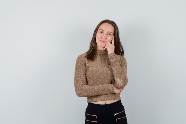 Młoda kobieta stojąca w myślącej pozie w złoconym swetrze i czarnych spodniach i patrząc szczęśliwy