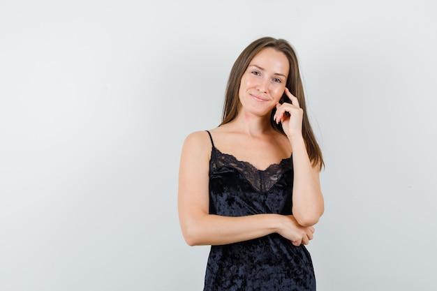Młoda kobieta stojąca w myśleniu gest w czarny podkoszulek i patrząc wesoło
