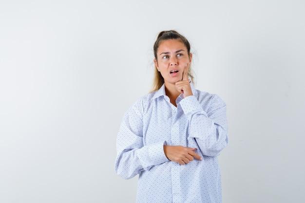 Młoda kobieta stojąca w myśleniu poza, opierając policzek na palcu wskazującym w białej koszuli i patrząc zamyślony