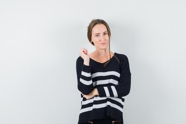 Młoda kobieta stojąca w myśleniu poza w czarną bluzkę i czarne spodnie i patrząc pewnie