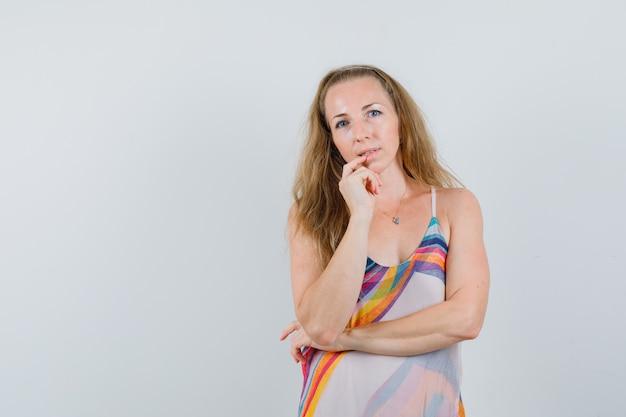 Młoda kobieta stojąca w myśleniu poza w letniej sukience i wyglądająca rozsądnie