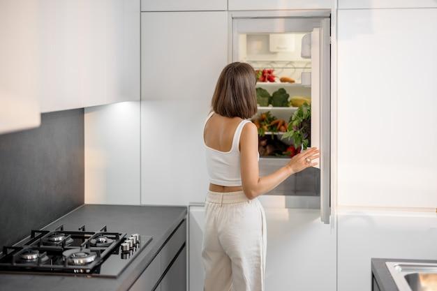 Młoda kobieta stojąca w pobliżu lodówki pełnej świeżych warzyw w nowoczesnej kuchni. koncepcja zdrowego wegańskiego jedzenia