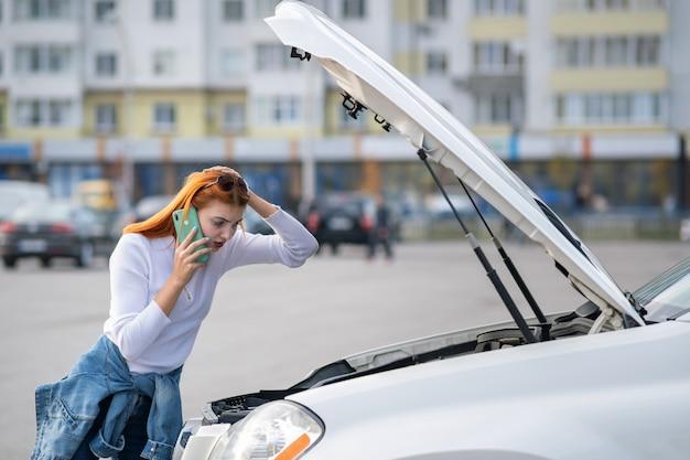 Młoda kobieta stojąca w pobliżu uszkodzonego samochodu z wyskakującym kapturem rozmawia przez telefon komórkowy