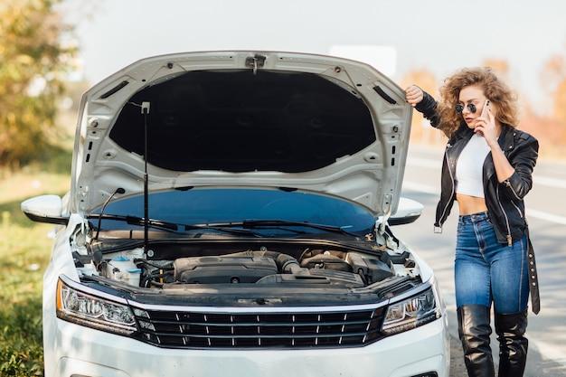 Młoda kobieta stojąca w pobliżu zepsutego samochodu z podniesionym kapturem rozmawia przez telefon komórkowy, czekając na pomoc.