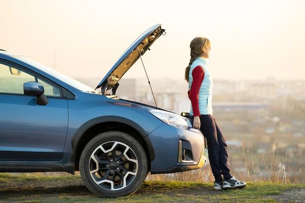 Młoda kobieta stojąca w pobliżu zepsutego samochodu z wyskakującą maską ma problem ze swoim pojazdem