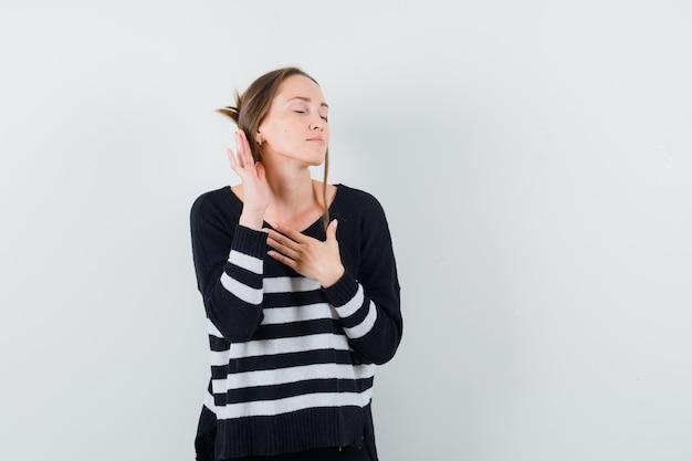 Młoda kobieta stojąca w pozie do słuchania, trzymając jedną rękę na piersi i zamykając oczy w pasiastej dzianinie i czarnych spodniach, wyglądając na szczęśliwą