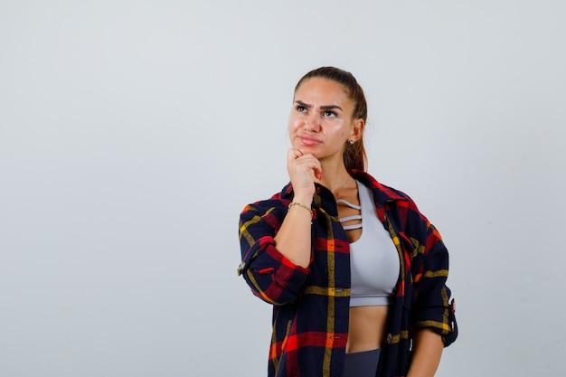 Młoda kobieta stojąca w pozie myślenia w topie, kraciastej koszuli, spodniach i zamyślonym spojrzeniu. przedni widok.