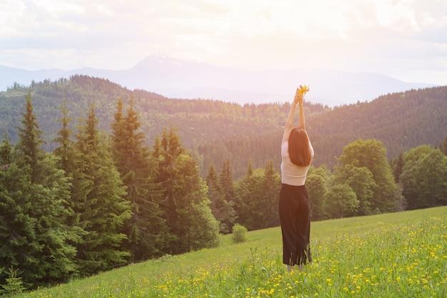 Młoda kobieta stojąca z bukietem kwiatów i podniesionymi rękami. las i góry w kosmosie. widok z tyłu