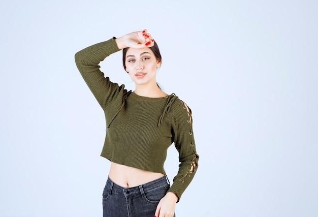 Młoda kobieta stojąca z poważnym wyrazem twarzy na białym tle.