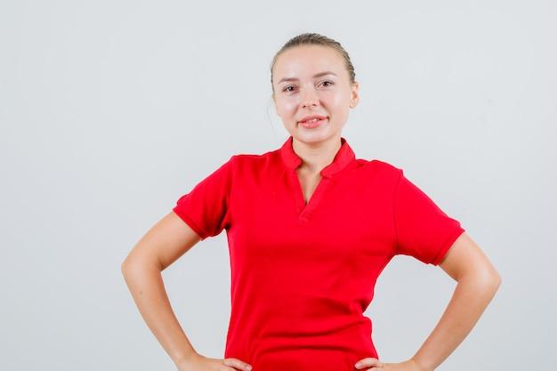 Młoda kobieta stojąca z rękami w pasie w czerwonej koszulce i patrząc pewnie