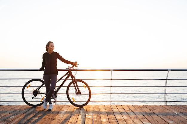Młoda kobieta stojąca z rowerem na promenadzie, podczas wschodu słońca nad morzem