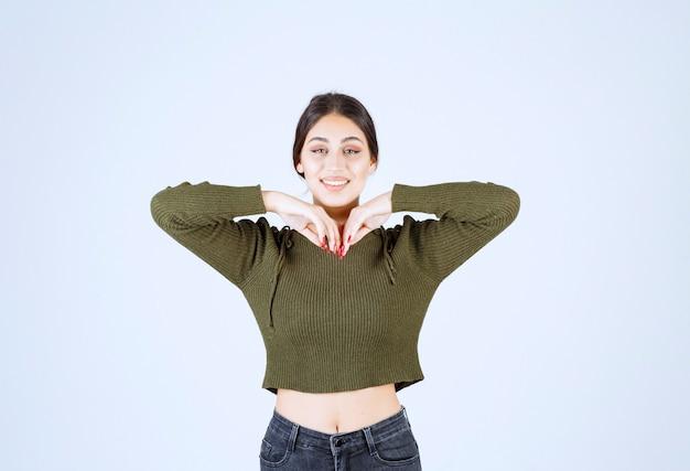 Młoda kobieta stojąca z szczęśliwym wyrażeniem na białym tle.