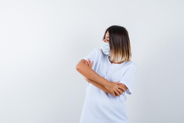 Młoda kobieta stojąca ze skrzyżowanymi rękami, patrząc w bok w t-shirt, masce i patrząc pewnie, widok z przodu.