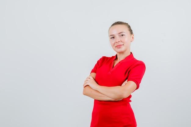 Młoda kobieta stojąca ze skrzyżowanymi rękami w czerwonej koszulce i patrząc wesoło