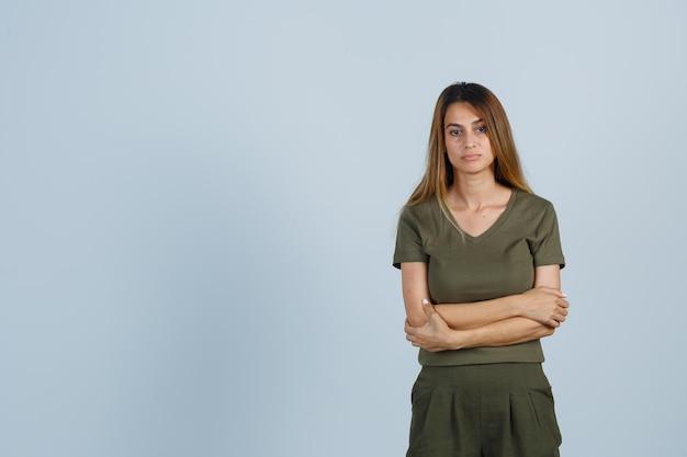 Młoda kobieta stojąca ze skrzyżowanymi rękami w koszulce, spodniach i patrząc smutno, widok z przodu.