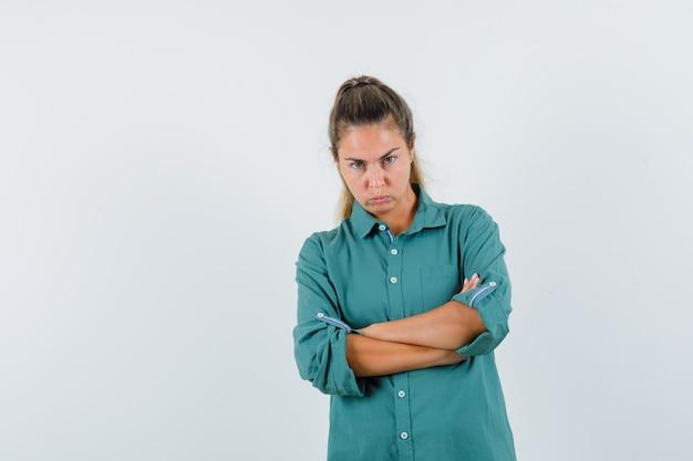 Młoda kobieta stojąca ze skrzyżowanymi rękami w niebieskiej koszuli i patrząc obrażony