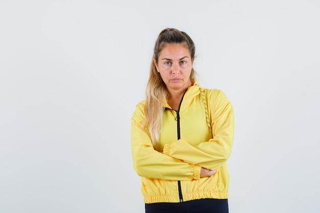 Młoda kobieta stojąca ze skrzyżowanymi rękami w żółtym płaszczu przeciwdeszczowym i patrząc poważnie