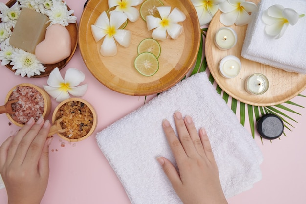 Młoda kobieta stosując naturalny peeling na rękach przed białą powierzchnią. zabieg i produkt leczniczy dla kobiecych dłoni, masaż, woda perfumowana i świece, relaks. leżał na płasko. widok z góry.