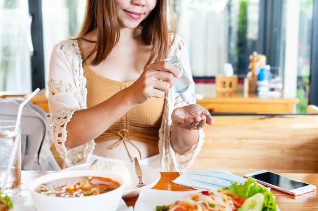 Młoda kobieta, stosując środek dezynfekujący do rąk na jej rękę przed jedzeniem w restauracji. koncepcja opieki zdrowotnej.