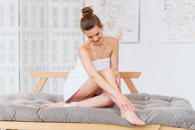 Młoda kobieta stosuje ciało śmietankę na ona nogi z gładką miękką skórą indoors, zbliżenie. pielęgnacja urody i ciała