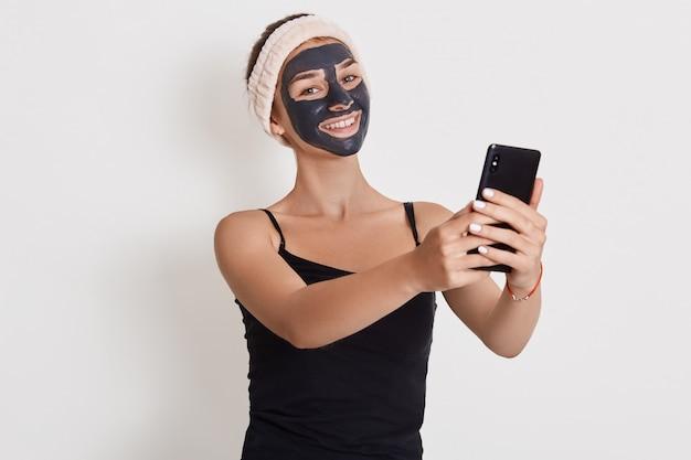 Młoda kobieta stosuje czarną kosmetyczną maseczkę na twarz i trzyma telefon w rękach odizolowanych na białej ścianie. maseczka peelingująca do twarzy, zabiegi upiększające w spa, pielęgnacja skóry, kosmetologia.