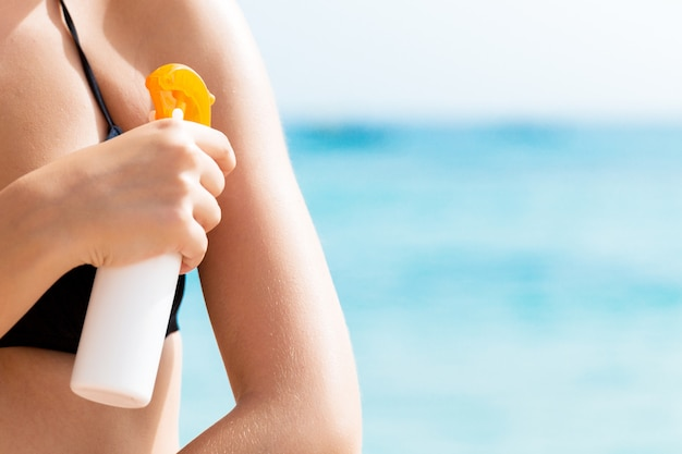 Młoda kobieta stosuje ochronną krem przeciwsłoneczny na jej ramieniu na plaży