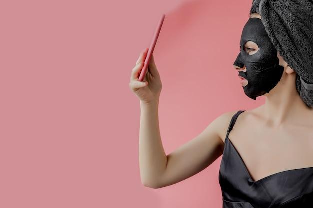 Młoda kobieta stosuje twarzową czarną tkaninę kosmetyczną maskę i telefon w ręce na różowej ścianie. maska peelingująca z węglem drzewnym, zabiegi kosmetyczne w spa, pielęgnacja skóry, kosmetologia. ścieśniać